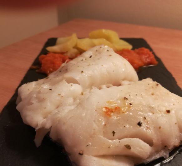 Merluza con patatas y salsa de tomate.